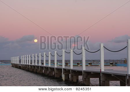 Full Moon Rising Over The Ocean At Sunset
