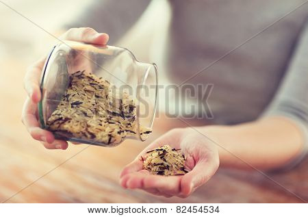 cooking and home concept - close up of female emptying jar with mixture of white and wild black rice
