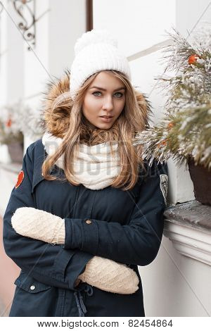 Beautiful Girl In A Knitted Hat And Jacket Standing Near The Wall With Christmas Decorations.