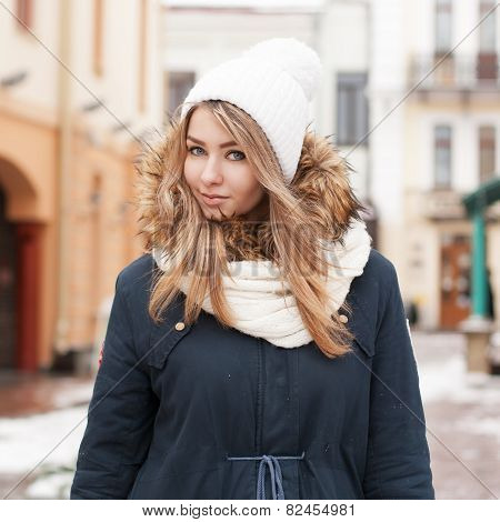 Pretty Girl In A Knitted Hat And Jacket. Stands Near A Shopping Center.