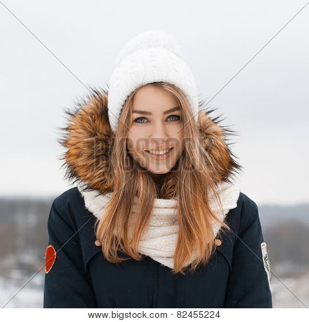 Sweet Girl In A Knitted Hat And Jacket Smiles.outdoors In Winter