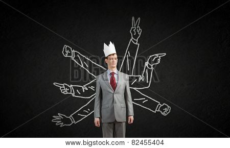 Young businessman in paper crown and many hands around him