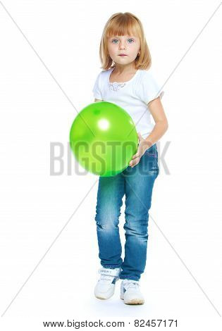 Little girl holding a green ball.