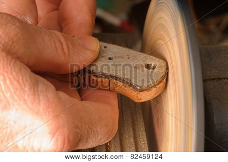 Knife maker sanding a wooden handle/grip to shape