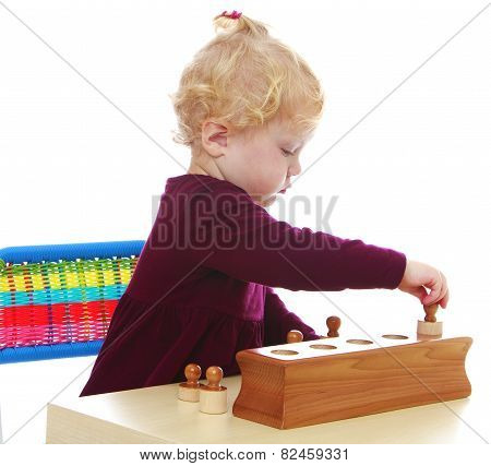 little girl playing puzzle sitting at the table.