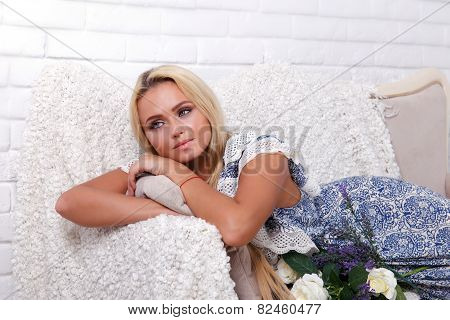 Blond Girl In Blue Sundress Lying On The Couch