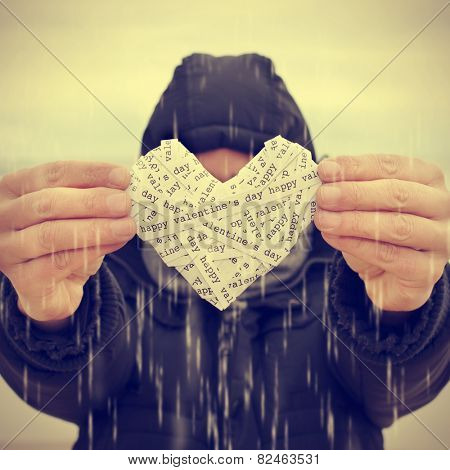 a young man under the rain showing a heart made-up with paper strips with the text happy valentines day, with a filter effect
