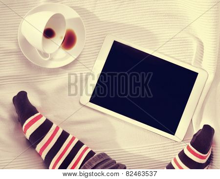 high-angle of the feet of a man and a cup of coffee and a tablet computer on a bed covered with a bedcover