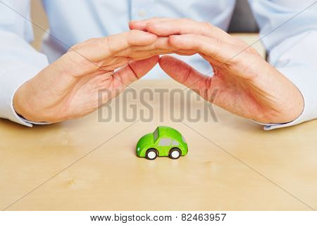 Two hands protecting a small green car as concept for car insurance