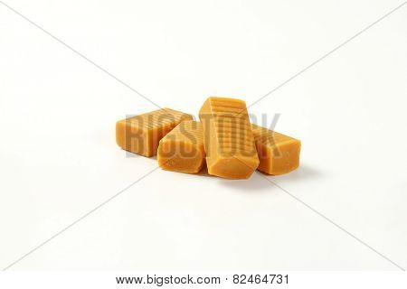 four caramel toffee candies on white background