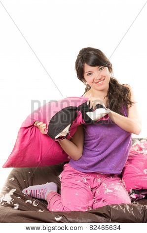 pretty young girl wearing pajamas having a pillow fight