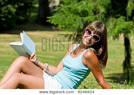 Happy Young Woman With Book In Park