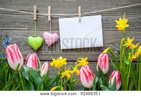 Message and hearts on the clothesline with spring flowers against wooden background