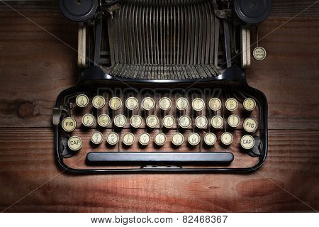 High angle shot of an antique typewriter on a rustic wood table. Closeup on the keys showing only part of the machine. Horizontal format with spot lighting.