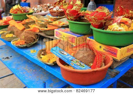 PATAN, NEPAL - APRIL 2014 : Bowls of religious offerings at Kumbeshwar Temple on 13 April 2014 in Patan, Nepal. Ritual offerings consist of offering dish, coconut, incense sticks, flowers, candles