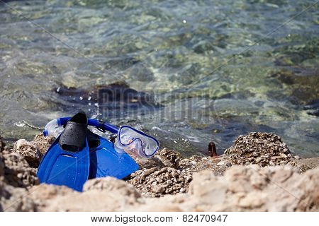 Mask and flippers on a rock beach