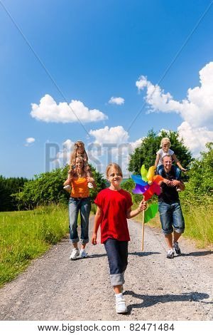 Family walking down a rural path on bright summer day