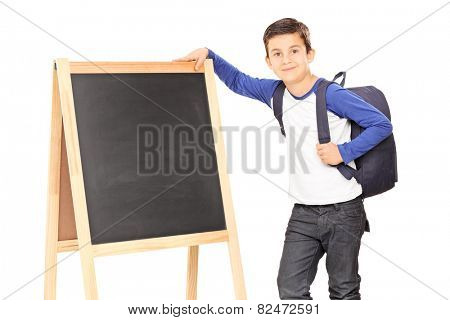 Schoolboy standing by a blackboard and carrying a backpack isolated on white background