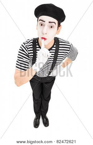 Mime artist holding a finger on his lips isolated on white background