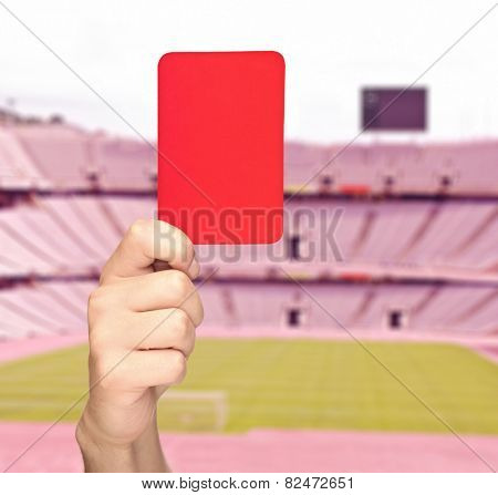 Hand holding a red card in front of an empty stadium shot with tilt and shift lens
