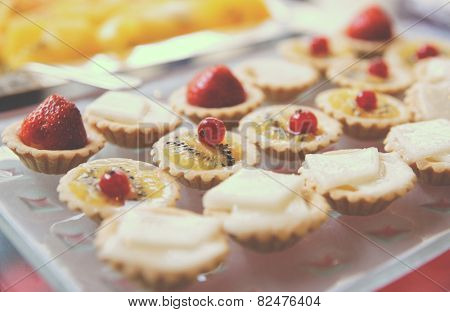 Sweets on banquet table - tartlets with white chocolate and berries, toned image