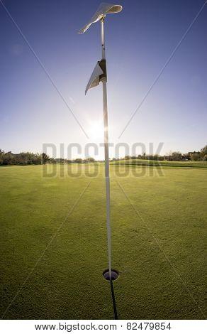 Putting green golf flag sun setting - extreme wide angle