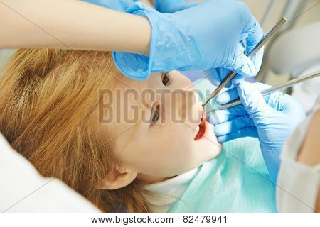 dentist orthodontist female doctor making dental care to child patient at working place
