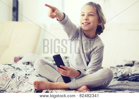 8 years old child watching tv, relaxed in parent's bed in morning at home