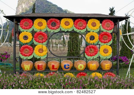 Welcome Sign In The Garden With Colorful Flowers On The Background