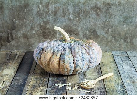 Pumpkin And Pumpkin Seeds In Wood Spoon On Wooden Background