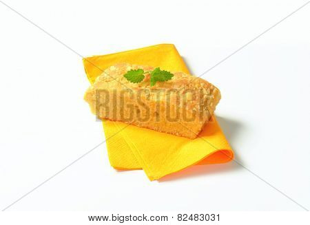 Slice of almond madeira cake on yellow serviette