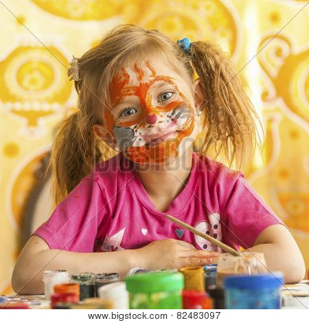 Child with a face painted with colorful paints (squares series)