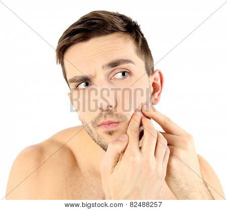 Handsome young man squeezing pimple isolated on white