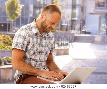 Young man sitting outdoors, using laptop at summertime.