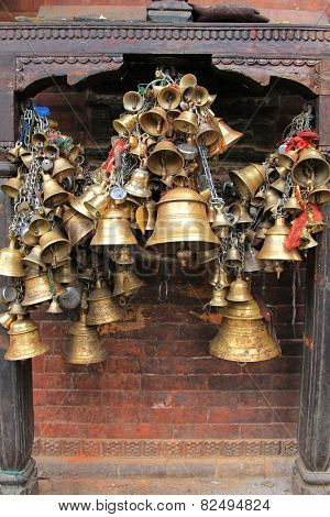 PATAN, NEPAL - APRIL 2014 : Metal sacrificial bells hanging on chain at Kumbeshwar Temple on 13 April 2014 in Patan, Nepal. Bell is one of the worship materials to Hindu Goddess.