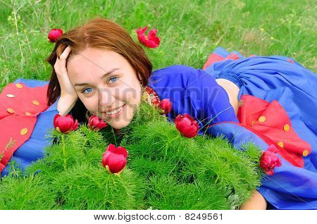 Gipsy Girl In Blue, Lying On Green Grass With A Flower