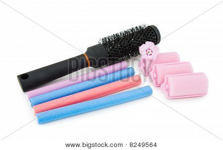 Hair Brush And Curlers On White