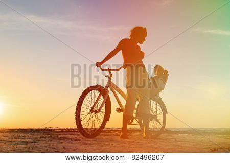 mother and baby biking at sunset