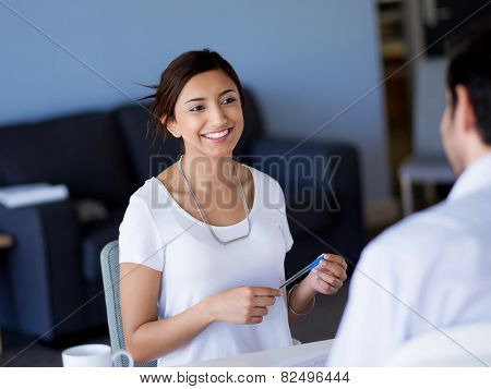 Young business woman talking to her collegue and smiling