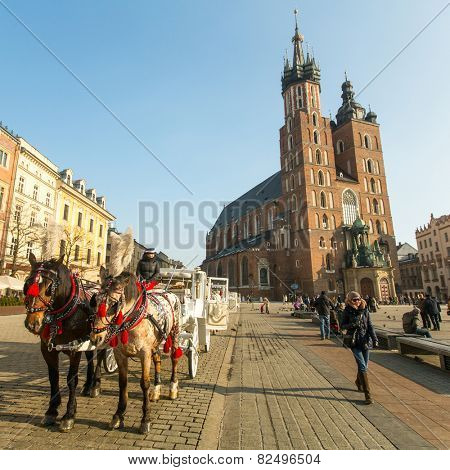 KRAKOW, POLAND - FEB 7, 2015: St. Mary's Church in historical center of Krakow on Main Square - dates to the 13th century, and at roughly 40,000 m it is the largest medieval town square in Europe.