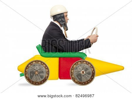 Young businessman driving fast on a toy car