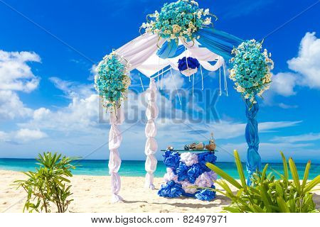 beautiful decorated wedding arch on sand beach, outdoor tropical wedding setup and venue