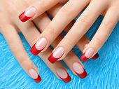 stock photo of french manicure  - Female hand with manicure and red french on nails - JPG