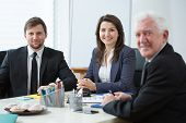 stock photo of assemblage  - Three happy businesspeople in conference room - JPG