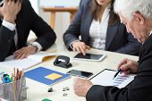 picture of assemblage  - Elderly businessman looking at poll results during business appointment - JPG