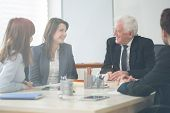image of assemblage  - Four elegant businesspeople on company meeting - JPG