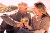 picture of couple sitting beach  - Couple enjoying white wine on picnic at the beach on a bright but cool day - JPG