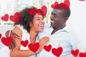 stock photo of cuddle  - Attractive couple cuddling on the couch against hearts hanging on a line - JPG