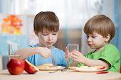 picture of kindergarten  - children eating  and drinking at home or kindergarten - JPG