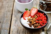 foto of breakfast  - fresh breakfast of granola yogurt nuts goji berries and strawberries - JPG